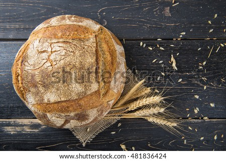 Homemade sourdough bread loaf decorated with burlap and cereal grains and ears