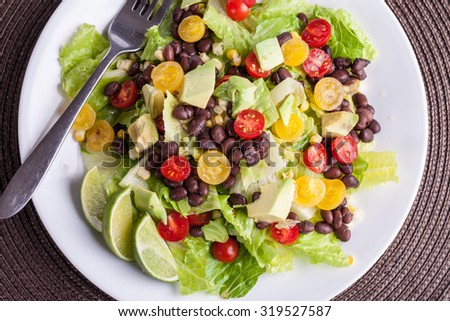 Homemade southwest black bean lime salad with corn, cherry tomatoes, lettuce, avocado, and black beans with vinaigrette dressing for clean eating - close up