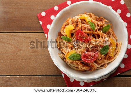 Homemade Spaghetti Bolognese with parmesan cheese in white bowl, on color wooden background - stock photo