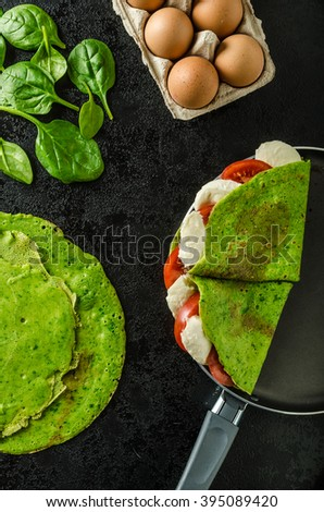 Homemade spinach crepes stuffed with basil, tomatoes and mozzarella - stock photo