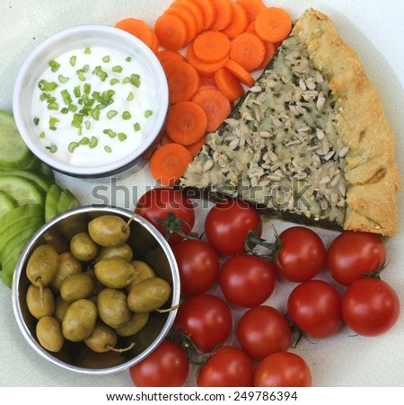 Homemade spinach pie served with white cheese dip, cherry tomatoes, cucumbers, carrots and Syrian olives, on a beige plate. - stock photo
