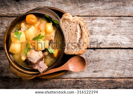 Homemade stew soup with vegetables and beef ribs in the rustic bowl,selective focus and blank space  - stock photo