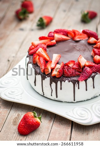 Homemade strawberry cake with chocolate icing on the white plate