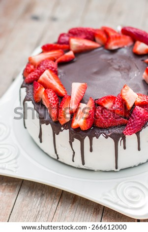Homemade strawberry cake with chocolate icing on the white plate - stock photo