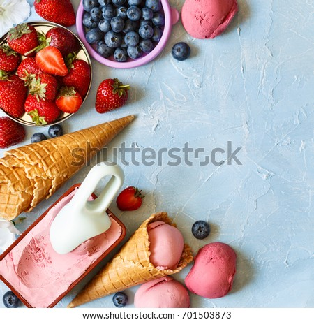 Homemade strawberry ice cream in the form and berries and waffle cones on frozen blue background.