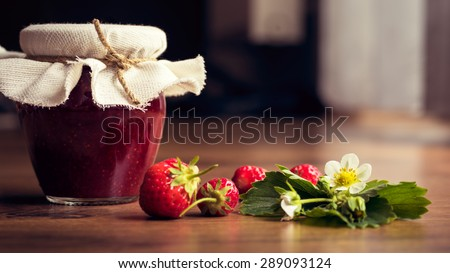 Homemade strawberry jam (marmalade) in jars on wooden background. - stock photo