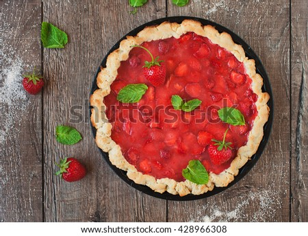 Homemade strawberry tart with cream cheese and mint on wooden background. Top view. - stock photo