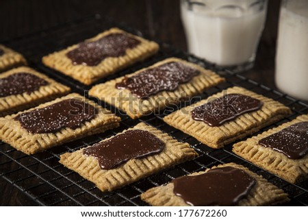 Homemade stuffed pastry with chocolate frosting on a dark wood table with milk in the background - stock photo