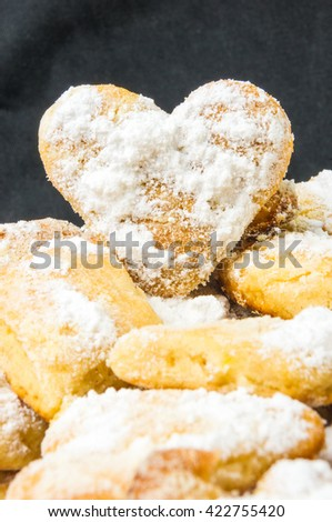 homemade sugar cookies in the shape of a heart on a black textile background - stock photo