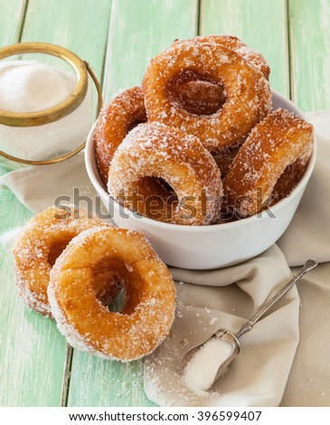 Homemade sugared cronuts in a bowl on a worn out wooden table