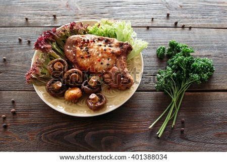Homemade supper with fresh vegetables. Grilled pork meat with lettuce and mushrooms. Homemade steak on wooden table.  - stock photo