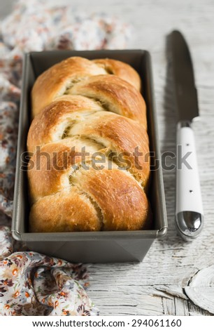 homemade sweet butter bread, brioche, in the baking dish on a light wooden background - stock photo