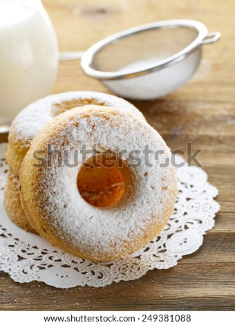 homemade sweet donuts with powdered sugar on a wooden table - stock photo