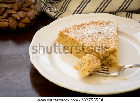 Homemade sweet lemon cake with almonds and oat flour, glass jar with almonds, slice with fork on white plate, old wood table