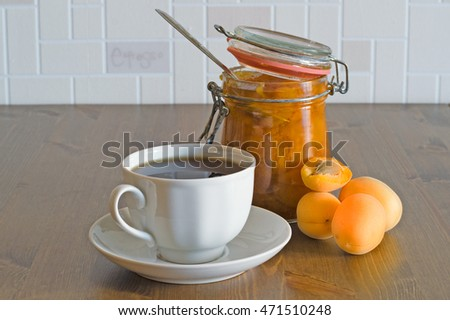Homemade sweet organic apricot jam in opened glass jar with apricots and white cup of tea on wooden table