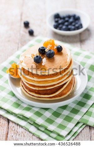 Homemade sweet pancakes with blueberries, fruit jam and honey on a white plate, closeup - stock photo