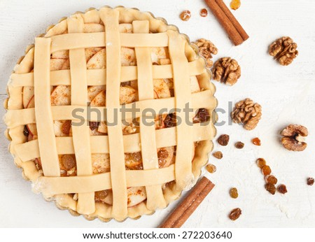 Homemade sweet pastry apple pie preparation. Raw tart with nuts, cinnamon and raisins on rustic white kitchen table - stock photo