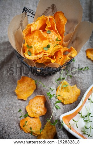 Homemade sweet potato chips with fresh thyme - stock photo