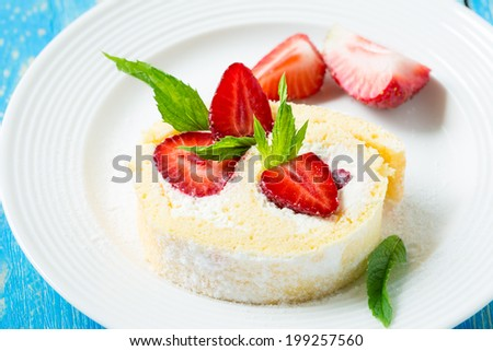 Homemade swiss roll biscuit cake with strawberries