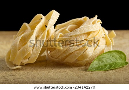 Homemade tagliatelle and basil on wooden table with black background - stock photo