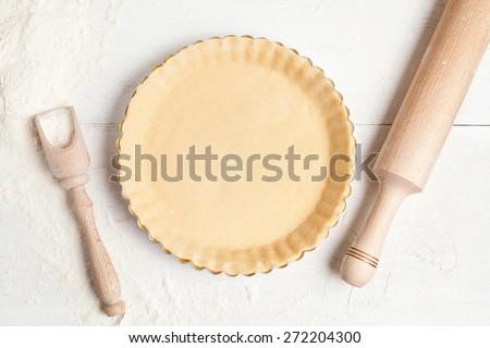 Homemade tart pie preparation, dough with yeast and rolling pin on white rustic kitchen table - stock photo