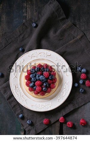 Homemade tart with custard, fresh raspberries and blueberries, served on white vintage plate on textile napkin over old wooden table. Dark rustic style. Flat lay - stock photo