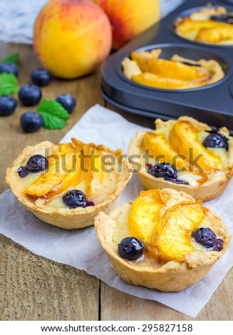Homemade tartlets with peach and blueberries - stock photo