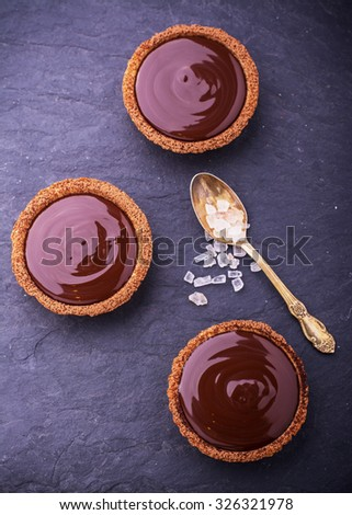 Homemade tarts of shortcrust pastry with dark chocolate and pink crystals of sea salt. Top view. selective Focus - stock photo
