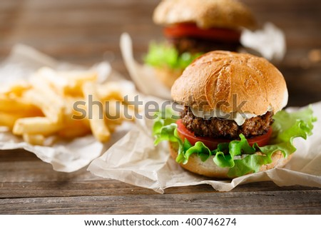 Homemade tasty burger and french fries on wooden table - stock photo