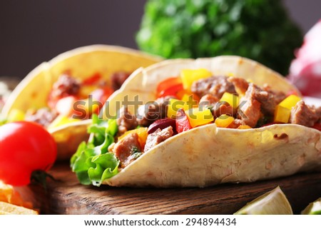 Homemade tasty burrito with vegetables on cutting board, on wooden background - stock photo