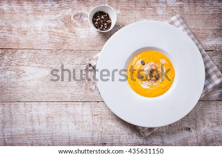 Homemade tasty creamy pumpkin soup puree in a bowl on a wooden background, copy space, top view - stock photo
