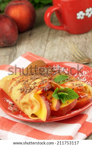 Homemade tasty crepes with peaches, chocolate and syrup