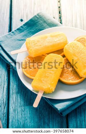 homemade tasty popsicle with fresh orange, vibrant blue and orange colors - stock photo