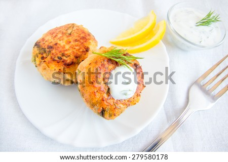Homemade thai fish cakes (cutlets) with white sauce, dill and lemon on plate - stock photo