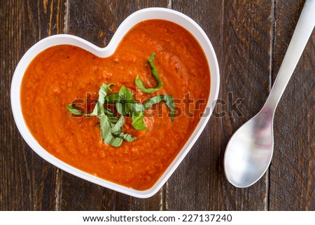 Homemade tomato and basil soup in white heart shaped bowl with spoon, whole wheat crackers, heirloom tomatoes and red heart napkin - stock photo