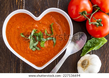 Homemade tomato and basil soup in white heart shaped bowl with spoon with fresh vegetables - stock photo