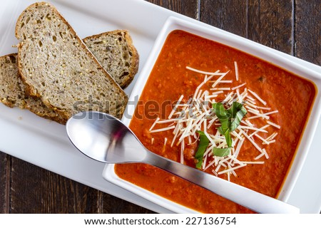 Homemade tomato and basil soup sprinkled with parmesan cheese in white square bowl and spoon, sitting on white platter with whole wheat bread slices - stock photo