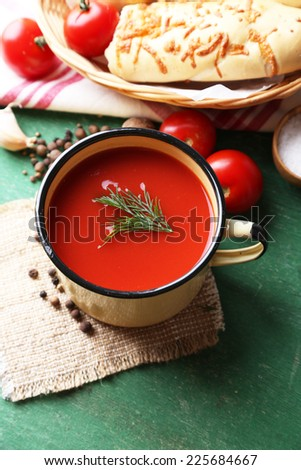Homemade tomato juice in mug, spices and fresh tomatoes on wooden background