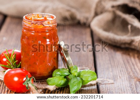 Homemade Tomato Sauce with basil and garlic on an old vintage table - stock photo