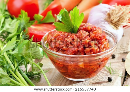 Homemade tomato sauce with pepper, onion and parsley in glass bowl on rustic wooden table - stock photo