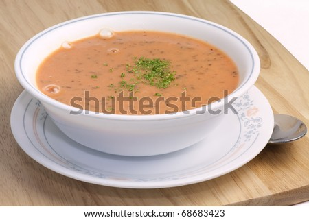 Homemade tomato soup with a sprinkle of parsley in a white bowl on a wooden cutting board.