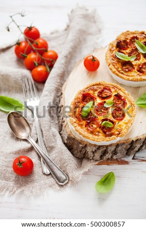 Homemade tomato tartlets with basil leaves