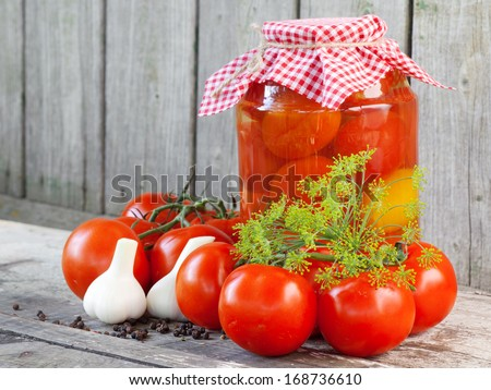 Homemade tomatoes in glass jar. Fresh and canned tomatoes on wooden board - stock photo