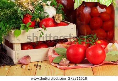 Homemade tomatoes preserves in glass jar and raw red tomatoes with dill and spices in crate