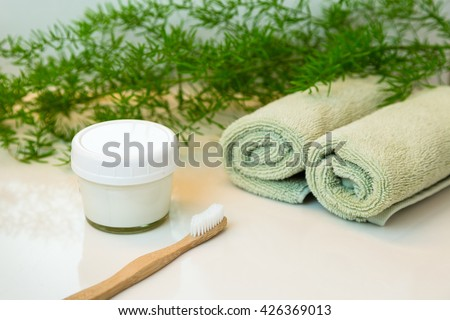 Homemade toothpaste in mason jar and bamboo bio-degradable, compostable toothbrush. Rolled green towels in a spa setting. Green plant decor in background. Bathroom white countertop.