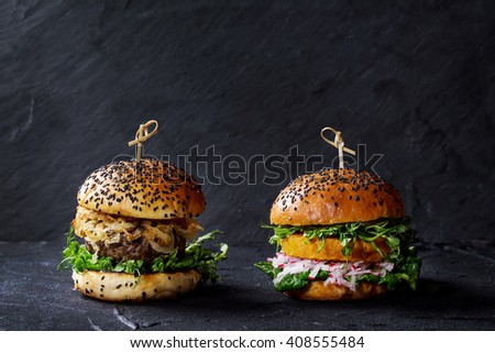 Homemade traditional and veggie burgers with beef, fried onion, sweet potato, radish and pea sprouts, served over black textured background. Healthy vs unhealthy concept food. Copy space - stock photo