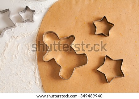 Homemade traditional gingerbread cookies dough preparation recipe on white kitchen table with cutting forms and flour. - stock photo