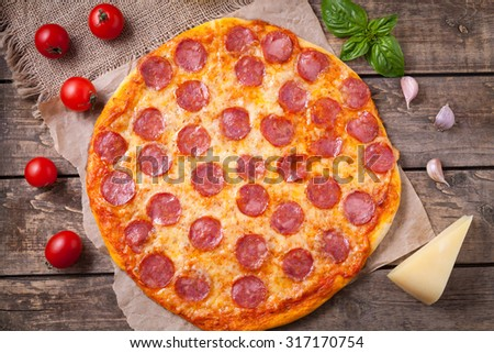 Homemade traditional mediterranean pizza with pepperoni and mozzarella cheese, tomatoes, basil and garlic on vintage wooden table background. Rustic style and natural light. - stock photo