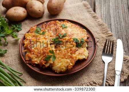 Homemade traditional potato pancakes or latke Hanukkah celebration food in rustic clay dish on vintage wooden background. Natural light - stock photo