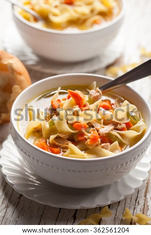 Homemade Turkey Noodle Soup with piping hot rolls close-up shot